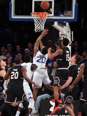 Seton Hall forward Desi Rodriguez (20) leaps in front of South Carolina guard PJ Dozier (15) to score the game-winning basket.