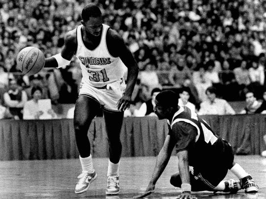 "Syracuse's Dwayne ""Pearl"" Washington dribbles past Georgetown's David Wingate after Wingate hit the floor trying to steal the ball from Washington in the second half of their baskeball game."