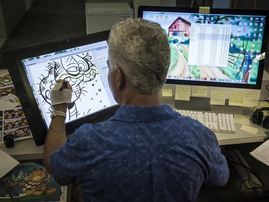 Paws, Inc. cartoonist Larry Fentz works at his desk in Albany.
