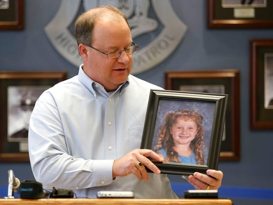 Tim Boatwright holds a photo of his daughter who was