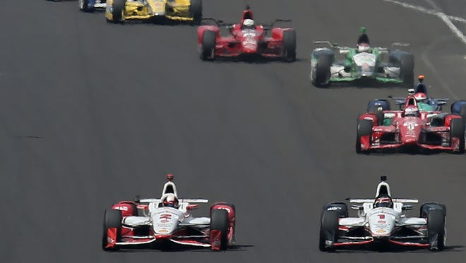 Juan Pablo Montoya (left) passes teammate Will Power to take the lead for good coming down the front straightaway at the Indianapolis Motor Speedway in the 99th running of the Indianapolis 500 on Sunday, May 24, 2015. Montoya came back from 30th position to beat Power by one-tenth of a second for his second Indy 500 win.