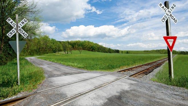 A narrow gravel road crosses a set of railroad tracks in rural Virginia.