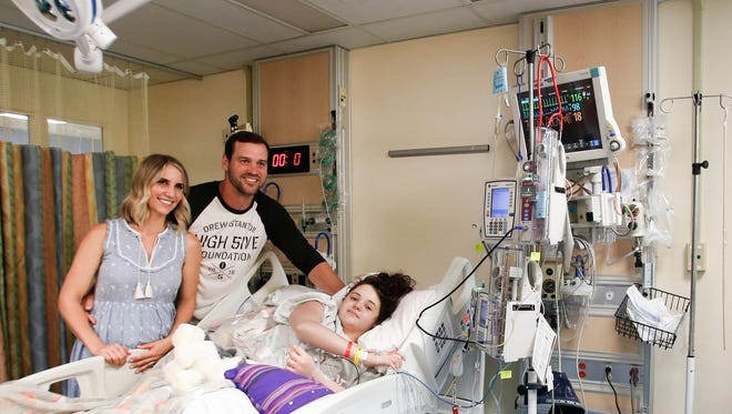 Former MSU QB Drew Stanton and wife Kristin get their photo taken with Sparrow Children's Center Miracle Child, inpatient Abbey Larkin, Thursday afternoon, June 15, 2017, at Sparrow Hospital.  The Drew Stanton High 5ive Foundation has helped support the Sparrow Children's Center, Pediatric Playroom, and Teen Lounge.