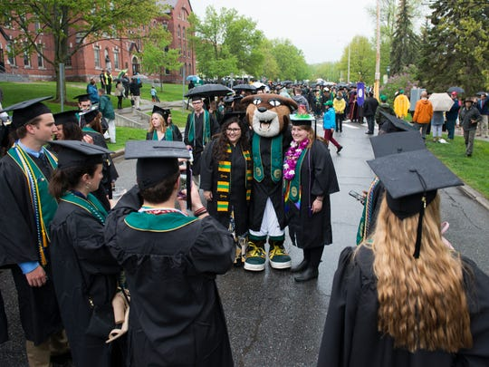 Graduates take a photo with UVM mascot Rally during the University of Vermont graduation ceremony on Sunday morning May 20, 2018 in Burlington.