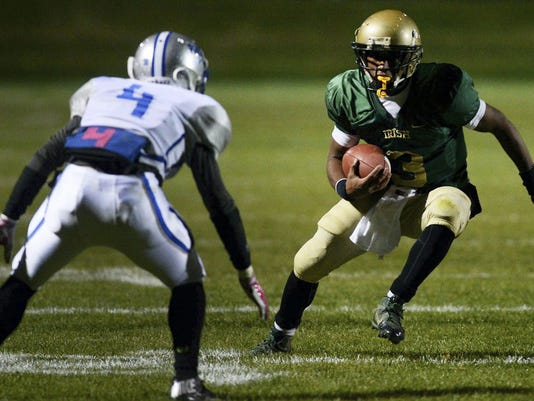 York Catholic quarterback Hakeem Kindard takes on Steelton-Highspire's Malachi Young to run for his second touchdown during the District 3 Class A football semifinal at York Catholic High School Friday, November 14, 2014. York Catholic won 23-8. Kate Penn — Daily Record/Sunday News