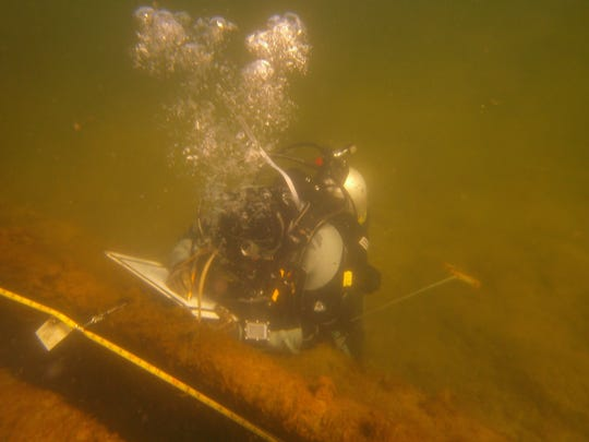An East Carolina student taking underwater measurements of the Fleetwing.
