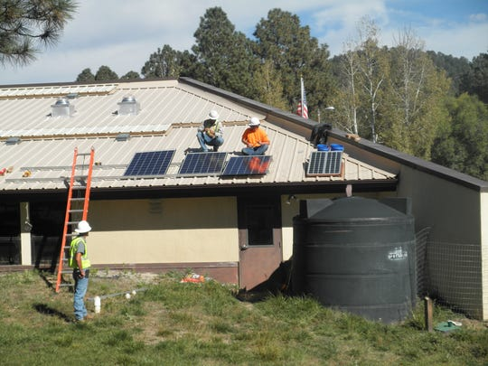 A crew installs solar panels on the roof of the main
