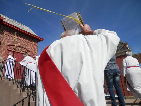The Gospel is carried up the stairs to the Episcopal Church of the Good Shepherd on Sunday during the Palm Sunday procession.