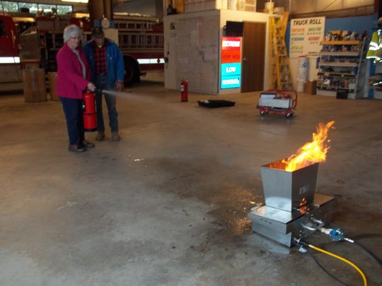 As pictured, Janet Kleinschmidt, Mutual of Wausau agent, tries out the new portable fire extinguisher trainer with help from Training Officer Len Francoeur.