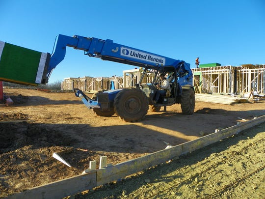A construction worker uses heavy equipment to move plywood for the 48-unit  Abbington Vista apartment complex being built on the outskirts of Henrietta.