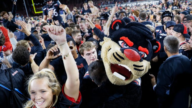 Cincinnati supporters storm the field after Cincinnati defeated UCF 27-24 in an NCAA college football game Friday, Oct. 4, 2019, in Cincinnati. (AP Photo/John Minchillo) ORG XMIT: OHJM118