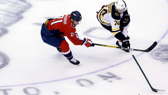Washington Capitals right wing Garnet Hathaway (21) vies for the puck with Boston Bruins left wing Jake DeBrusk (74) during first-period NHL Stanley Cup qualifying round game action in Toronto, Sunday, Aug. 9, 2020.