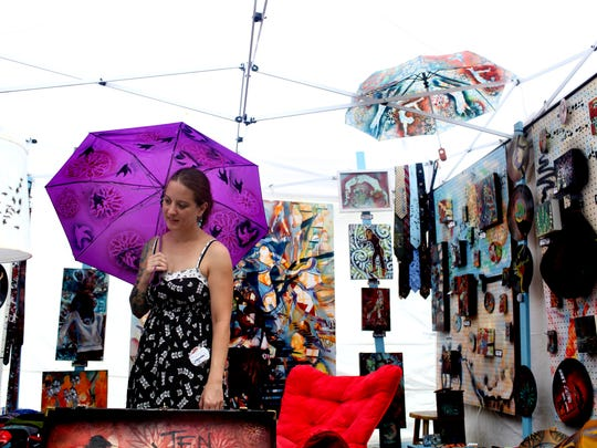 Artist Jennifer Goodell sells various painted items, including umbrellas, during the St. James Court Art Show. October 5, 2013