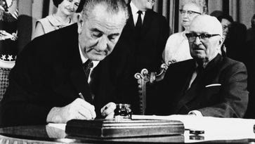 President Lyndon Johnson signs the Medicare Bill into law while former President Harry S. Truman observes during a ceremony at the Truman Library in Independence, Missouri, in 1965.