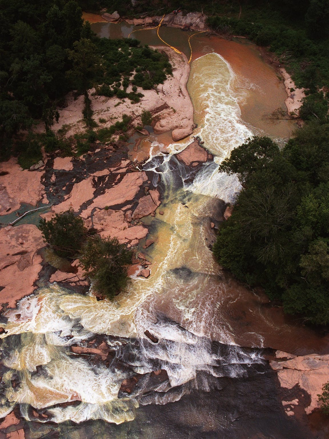 Contaminated water flows in the Reedy River toward