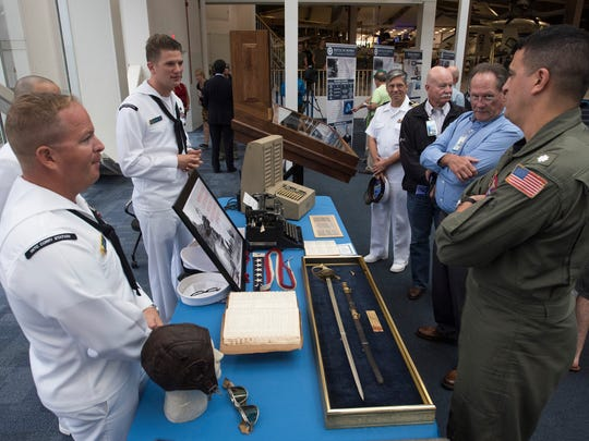 Petty Officer 1st Class, Scott Searcy, left, gives the history of the types of items on display at the National Naval Aviation Musem used by Navy code breakers during the Battle of Midway.