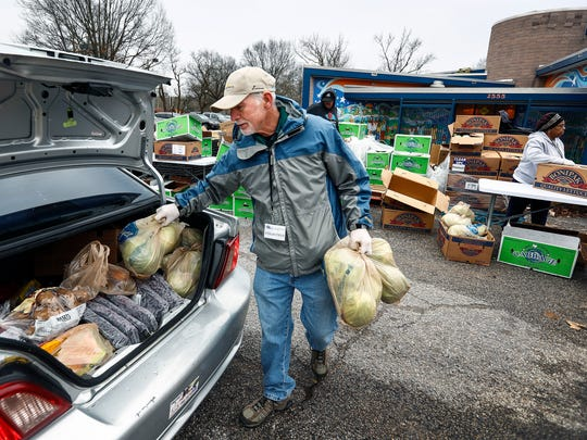 Mid-South Food Bank volunteer Jesse McCabe loads a car trunk with cabbage  during a food distribution at the North Frayser Community Center Friday morning.