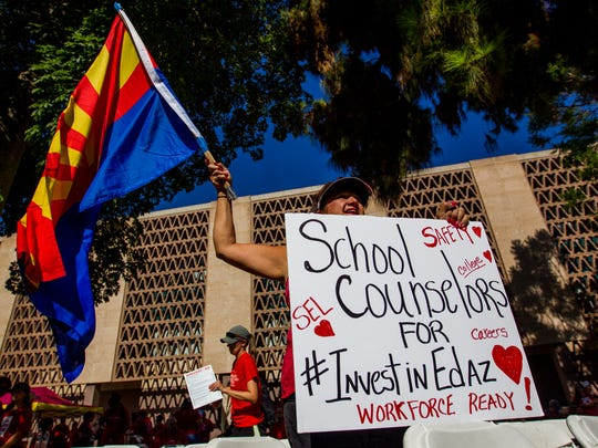Anna Cicero, a retired school counselor from Chandler, waves an Arizona flag on June 23, 2018, during a RedforEd rally outside of the Arizona State Capitol in Phoenix.