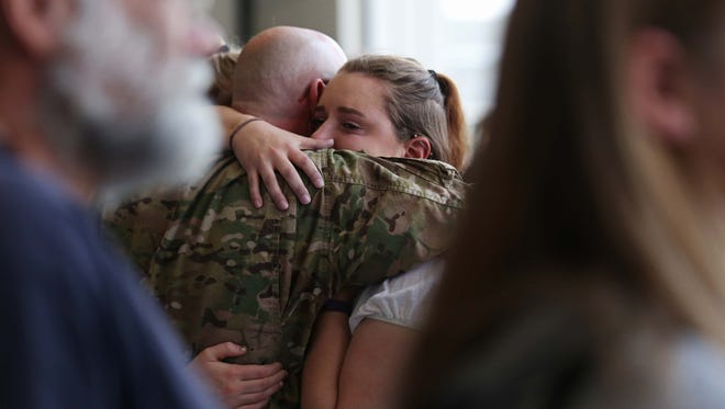Troy May, a member of the 185th Combat Sustainment Support Battalion of the Iowa Army National Guard, hugs one of his daughters, Alex May, during a send-off ceremony for the battalion May 8, 2016, at the Iowa National Guard's Des Moines Airbase.