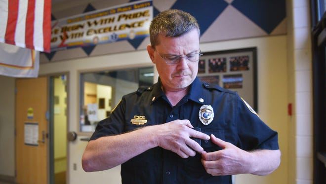 Mitchell Assistant Police Chief Michael Koster shows a generation one body camera Tuesday, June 12, at the police department in Mitchell.