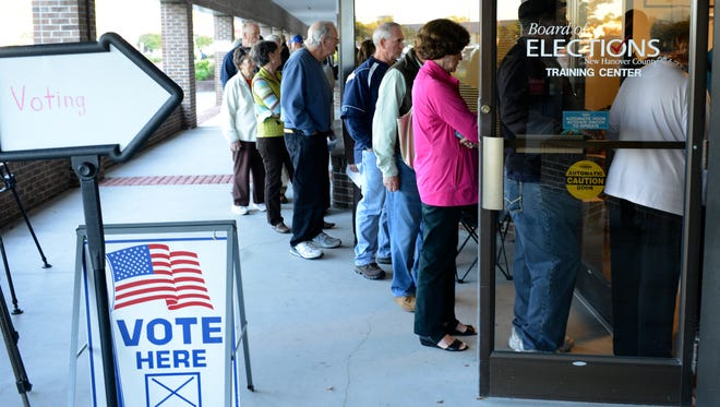 Voters line up outside the New Hanover County Board of Elections office as early voting began Oct. 23, 2014, in Wilmington, N.C.