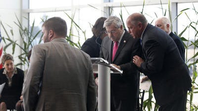 Gov. Terry Branstad is steadied during a speaking event at DuPont Pioneer Monday, Jan. 26, 2015. He was later hospitalized with a viral illness, and was released from the hospital on Tuesday.