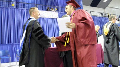 Graduate Nate Schweers, right, holds on to his diploma and is congratulated by Ankeny High's principal, Jeff Hawkins, during the May 2014 commencement ceremony.
