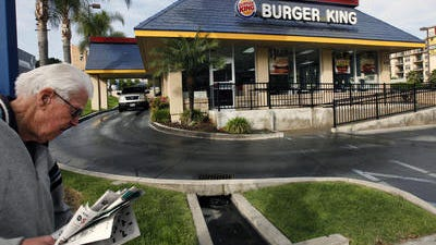 In this Thursday, April 25, 2013, file photo, a pedestrian walks past a Burger King restaurant near downtown Los Angeles. On Friday, April 25, 2014, Burger King reported a higher first-quarter profit as cost-cutting offset weak sales in the U.S. The Miami-based chain said global sales at established locations rose 2 percent, including a 0.1 percent increase in the U.S.