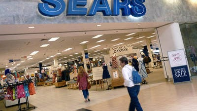 In this Monday, May 14, 2012, file photo, shoppers walk into Sears in Peabody, Mass. Searsâ?? first-quarter loss widened as the beleaguered retailerâ??s sales declined amid its ongoing struggle to attract shoppers.