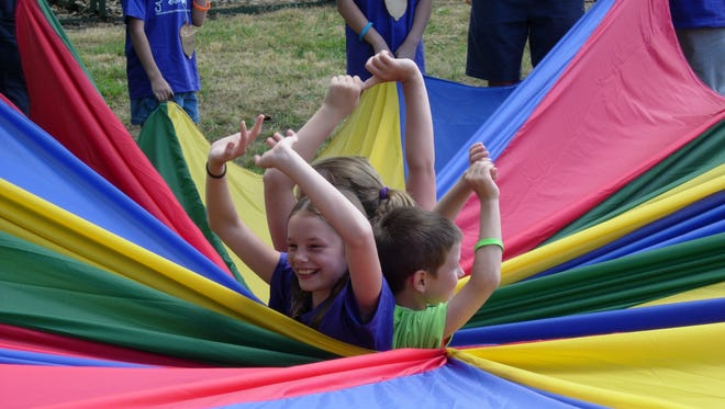 Campers play with a parachute at Camp Mighty Oaks, Willamette Valley Hospice's summer camp for families who have lost a loved one. This year the camp will be held Saturday, July 26, 2014.