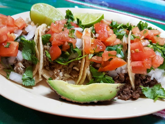 Tacos El Borrego de Oro, offer tacos for just $1 each on Taco Tuesdays. Pictured are two beef and two pork tacos. The special comes with lime, avocado, cilantro, tomato and onion.