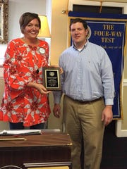 Josh Raffini receives the Rotarian of the Year Award by new club president Jeanie Campbell.