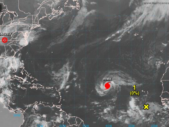 A tropical disturbance follows Hurricane Irma as she