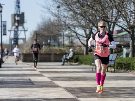 Women's overall winner Liz Swierzbinski runs along the riverfront walk in the Caesar Rodney Half-Marathon on Sunday morning.