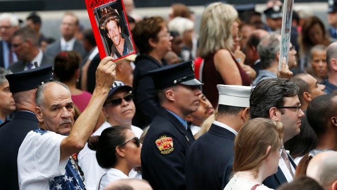 A mourner holds a photo of their loved one during the 15th anniversary of the attacks of the World Trade Center at the National September 11 Memorial, Sunday, Sept. 11, 2016, in New York.