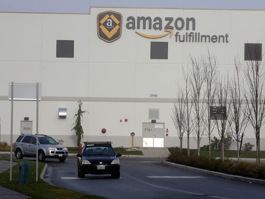 In this Nov. 30, 2015, file photo, cars drive away from Amazon.com's fulfillment center in DuPont, Wash. Buying things online could soon get pricier for many people after the U.S. Supreme Court's decision Monday, Dec. 12, 2016, not to get involved in a case that may lead to states collecting billions in lost sales taxes.