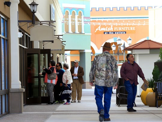 Shoppers walk around during the grand opening of the