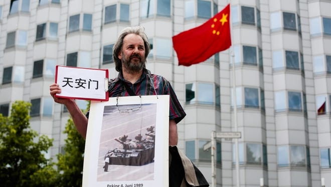 File picture - A protester covered with a photo and holding a poster with the Chinese letters for 'Tiananmen Square' as he protests in front of the Chinese Embassy in Berlin, Wednesday, June 4, 2014.