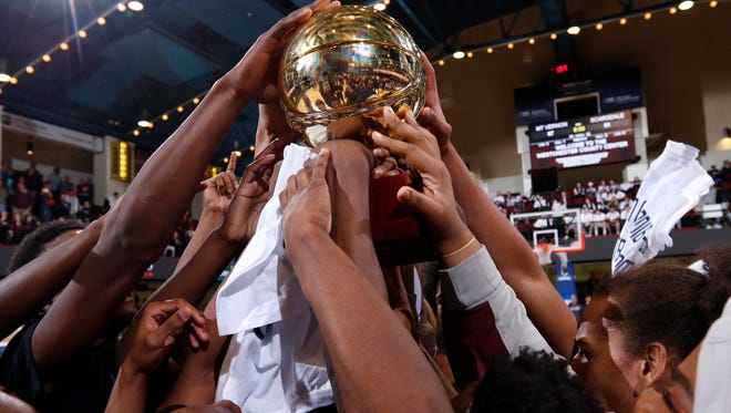 Mount Vernon player hoist the gold ball after their 67-61 overtime win over Scarsdale in the Section 1 Class AA boys championship basketball game at the Westchester County Center in White Plains on Sunday, March 5, 2017.