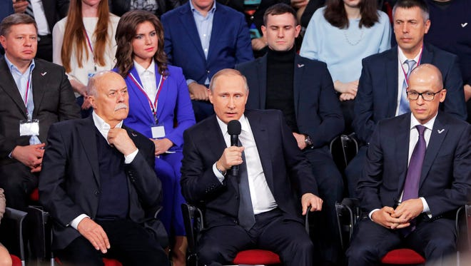 Russian President Vladimir Putin (center) speaks at a media forum of the All-Russia People's Front in St.Petersburg on April 7, 2016.