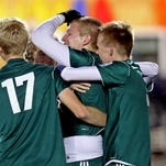 Brossart defender Dylan Geiman is mobbed by his teammates after scoring on a penalty kick for the Mustangs.