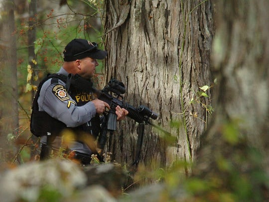 A Pennsylvania State Trooper searches the woods near Lower Swiftwater Road in Swiftwater, Pa on Saturday, Oct. 18, 2014 during a massive manhunt for killer Eric Frein.