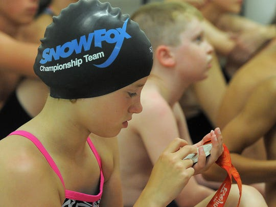 Justice Lloyd looks at one of Kara Lynn Joyce's Olympic silver medals during a swimming clinic at the at EmBe Fitness and Aquatic Center on Thursday to kickoff this weekend's Snowfox Independence Invitational.
