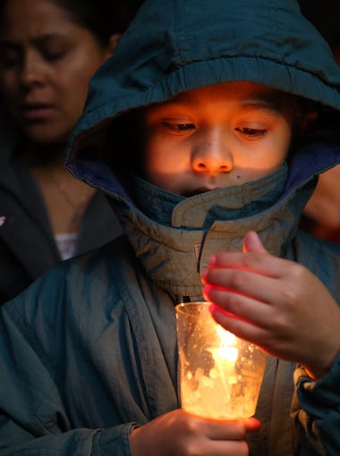 Eight-year-old Alonso Vidal holds a candle during the All Saints Episcopal Church celebration of Las Posadas, Monday, December 21, 2015, in Lakewood.