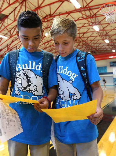 Fernando Barron, left, and Isaiah Harris compares class schedules after picking them up Monday morning in the gym at Brown Middle School. EPISD started classes on Monday.