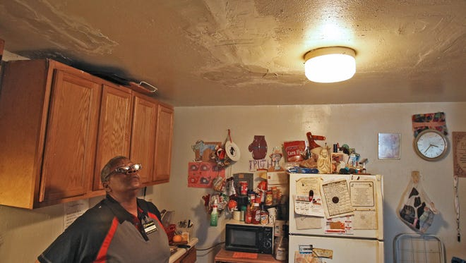 Renee Jones, 54, looks up at her ceiling, which she said was drywalled earlier Monday to repair water leaks. Jones, who has lived at The Alms for 12 years, appeared before City Council to describe  living conditions at the Walnut Hills apartment building on Monday.