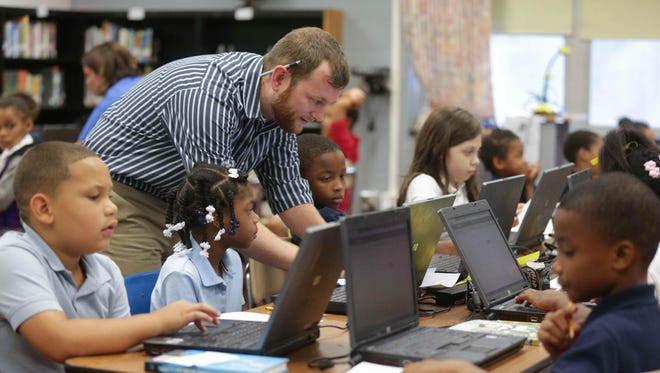 Teacher Mark Cassoday gets students started on a Project Restore math test at Indianapolis Public School No. 93 on Aug. 6, 2015. The school is part of Project Restore, which features a teacher-run curriculum where students at struggling schools are challenged with academic expectations higher than the districts curriculum, to develop academic skills on par with successful schools.