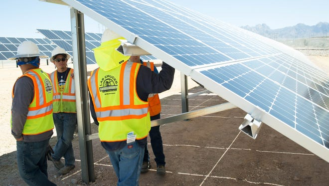 East Mesa Water Reclamation Plant employees, get some shade under the solar panels during the ribbon-cutting ceremony for the new Photovoltaic power system, Friday April 21, 2017.