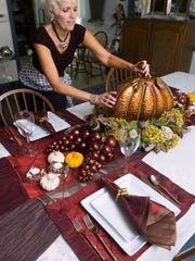 Judy Brillhart, at her Strawberry Shop, places a copper pumpkin and demonstrates how things can be reused to make different holiday and winter place settings.
