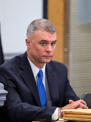 Lt. Mark Byrd sits at the Civil Service Board meeting at Asheville City Hall Wednesday, Nov. 19, 2014. Byrd and his attorney, John Hunter, say he was transferred to an administrative job after raising concerns about downtown staffing.